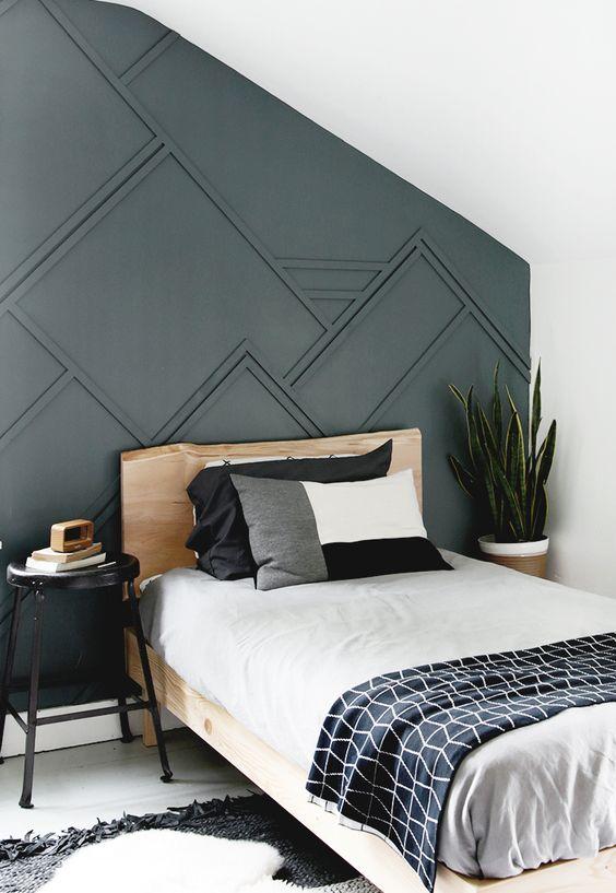 une chambre d'amis avec un mur lambrissé gris graphite, un lit en bois, une literie graphique et une plante remarquable dans le coin