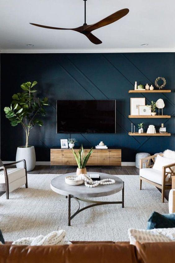un salon cool avec un mur d'accent lambrissé bleu marine, des meubles en bois, une table ronde accrocheuse et de la verdure en pots