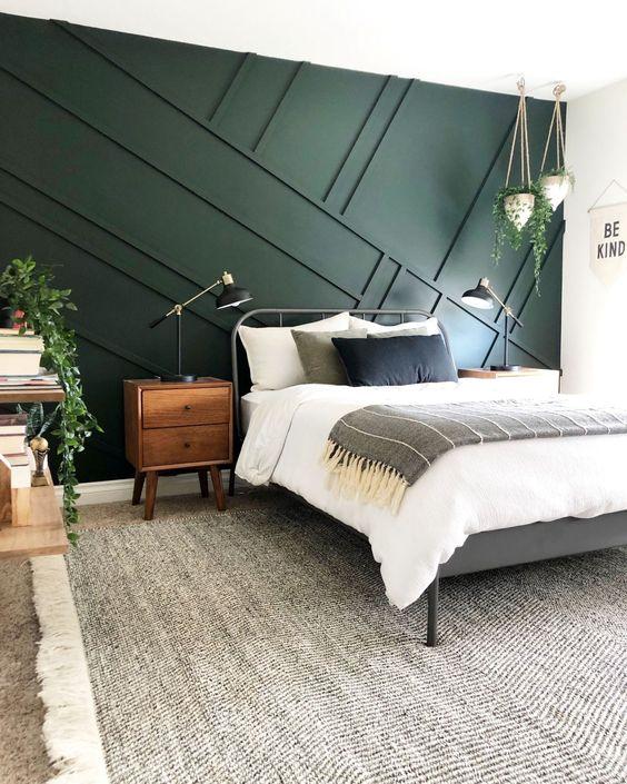 une chambre moderne du milieu du siècle avec un mur de panneaux géométriques vert foncé, un lit en métal, des meubles en bois et de la verdure dans des pots pour l'animer
