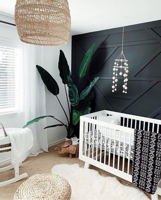une pépinière monochromatique avec un mur lambrissé noir, des meubles blancs, une suspension et un pouf en osier et une plante de déclaration