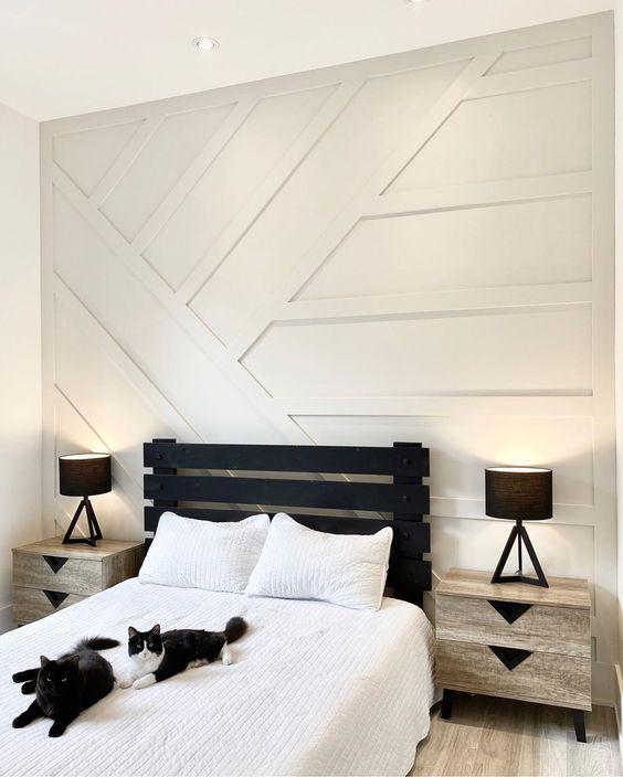 une chambre d'amis monochrome avec un mur lambrissé blanc, un lit noir et des tables de chevet neutres est une idée chic et audacieuse