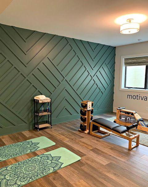 une salle de gym à domicile réalisée avec un mur lambrissé géométrique vert en guise de déclaration et tout le reste du décor qui l'entoure