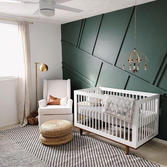une pépinière moderne du milieu du siècle avec un mur lambrissé vert, des meubles neutres, des poufs en osier, un mobile en bois et un lampadaire en laiton