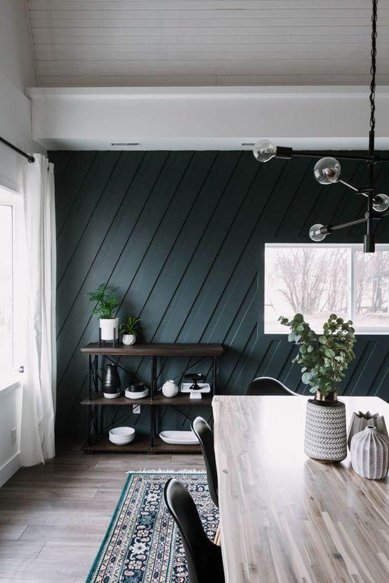 une salle à manger moderne du milieu du siècle avec un mur lambrissé géométrique vert chasseur, une étagère industrielle, une table en bois et un lustre accrocheur