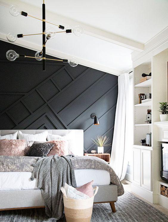 une élégante chambre moderne du milieu du siècle avec un mur lambrissé noir, un lit rembourré, des étagères intégrées et un lustre élégant