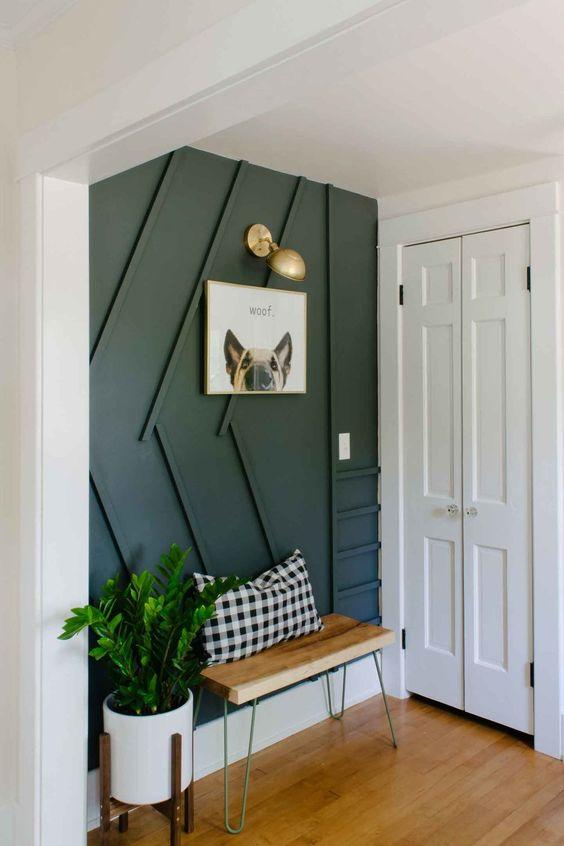 une entrée contemporaine élégante avec un mur lambrissé noir, un petit banc, une applique et de la verdure en pot est très cool