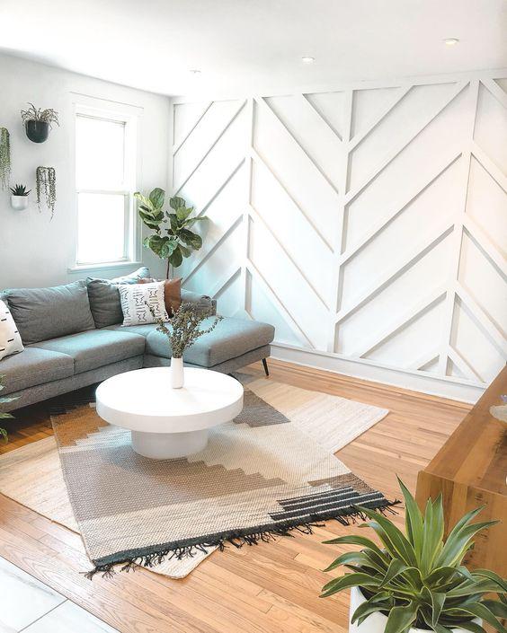 un salon éthéré avec un mur lambrissé géométrique blanc, un sectionnel gris, des meubles en bois, des tapis en couches et de la verdure en pot