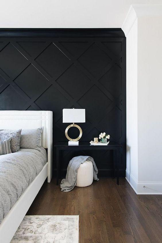 une chambre monochrome raffinée avec un mur lambrissé géométrique noir, un lit blanc, une table de chevet noire, un pouf blanc et une lampe chic