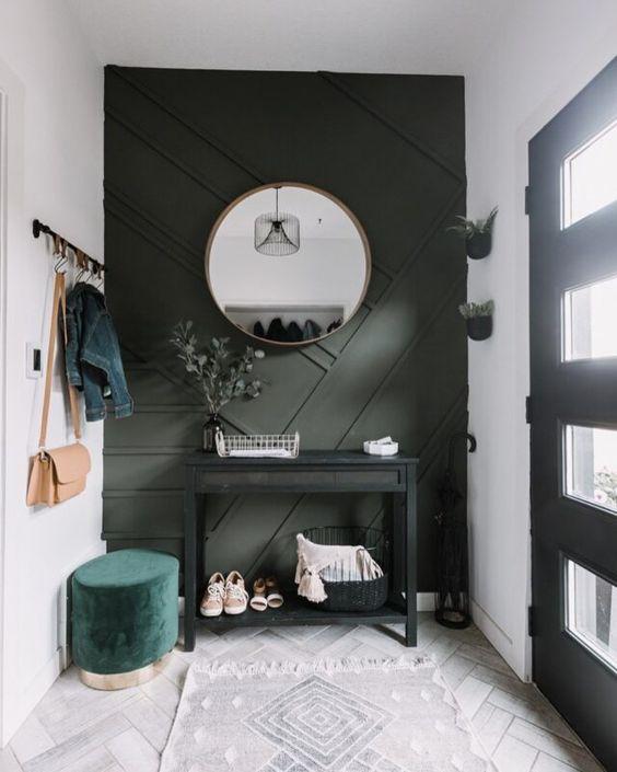 une petite entrée moderne avec un mur géométrique vert foncé, une console noire, un pouf vert et de la verdure en pot