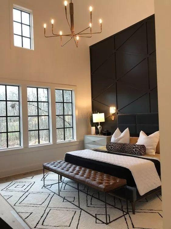 une chambre raffinée avec un mur géométrique lambrissé noir, un lit rembourré noir, un banc en cuir et un lustre accrocheur