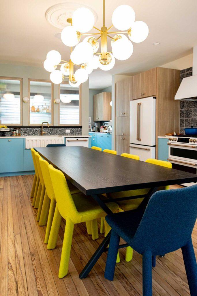La cuisine à manger présente des armoires bleues et blanches, une table à manger en bois et des chaises jaunes et bleues