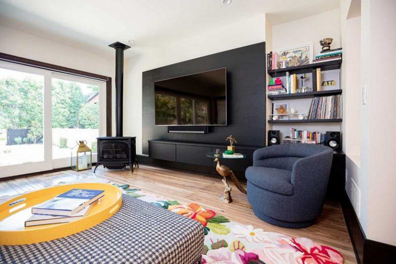 Le salon avec un mur vitré, qui est un accès à l'extérieur, un foyer et des pièces colorées est très accueillant