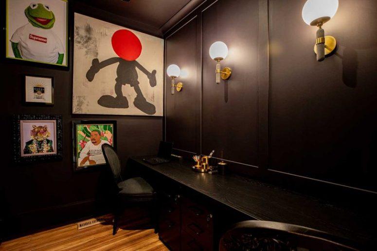 Le bureau à domicile est tout sombre, avec un bureau partagé, quelques chaises noires et un mur de galerie lumineux