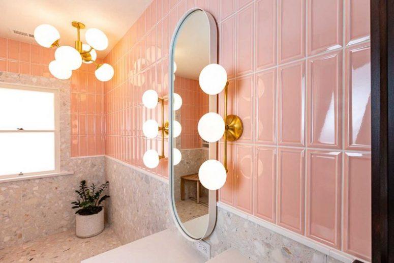 La salle de bain est faite avec des carreaux roses et terrazzo, avec des lampes rétro et un lustre et un miroir incurvé