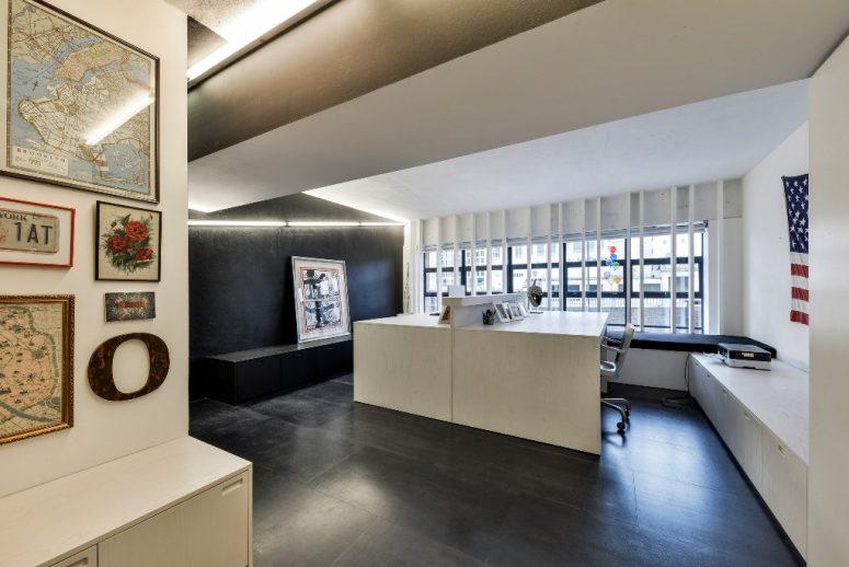 Le bureau à domicile est noir et blanc, avec deux bureaux blancs, des lumières intégrées et des unités de rangement intégrées