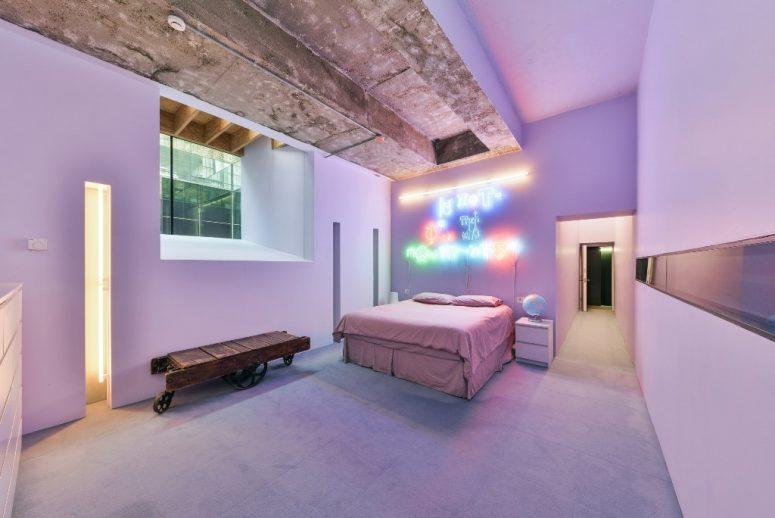 La chambre aster est rose et lavande, avec une enseigne au néon et un plafond en béton brut
