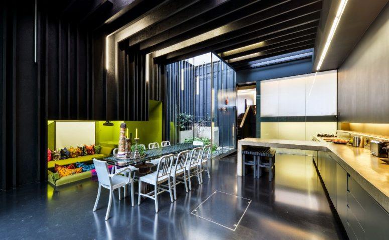 La zone de la cuisine-salle à manger se fait avec une fosse de conversation en contrebas avec des murs vert lime et des oreillers lumineux