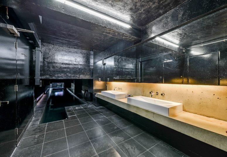 La salle de bain est toute noire, avec une vanité en pierre et des carreaux et d'autres surfaces en noir
