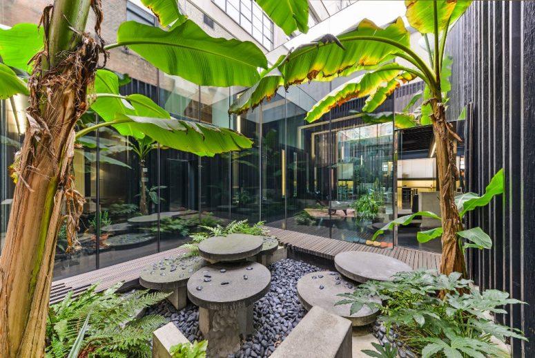 Une cour intérieure est comme un jardin, avec des arbres tropicaux, des galets et des meubles en pierre