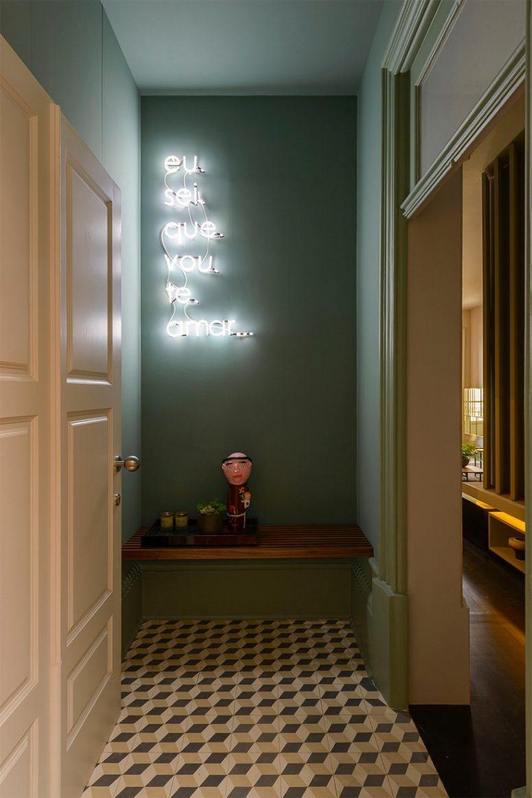 L'entrée est faite avec des murs verts, un sol géométrique, un banc et une enseigne au néon et elle a l'air audacieuse et fantaisiste