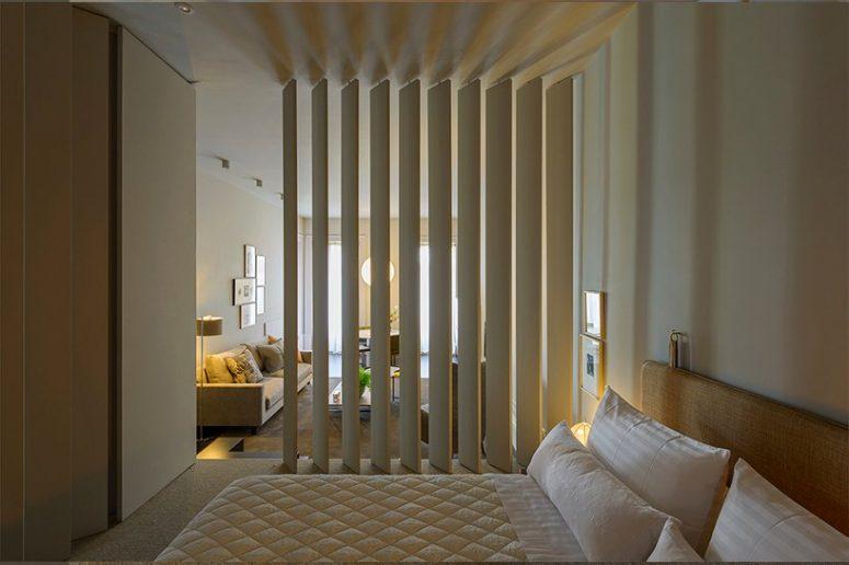 La chambre est neutre, avec des meubles blancs, une grande armoire élégante et des lampes et des œuvres d'art