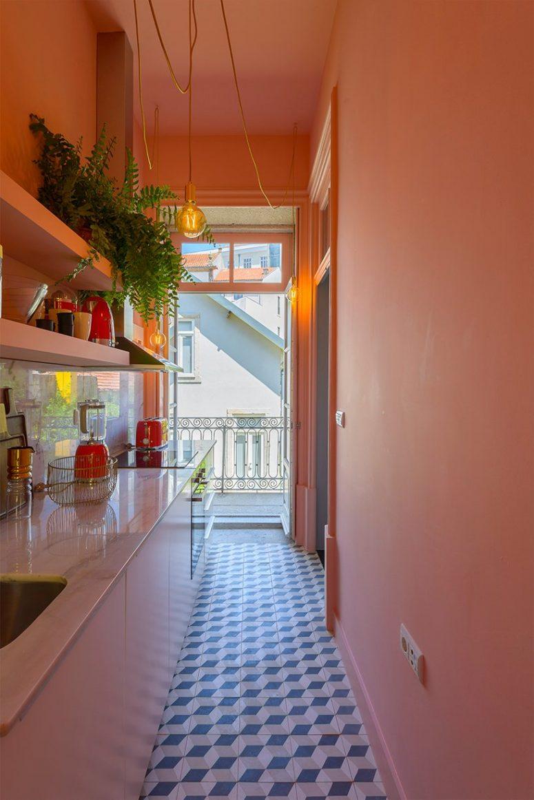 Les appareils rouges et autres touches ajoutent de la couleur à la cuisine, et une entrée de balcon la remplit de lumière naturelle
