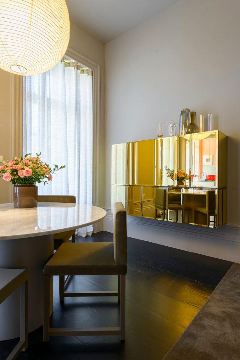 La salle à manger est très raffinée, avec une table ronde avec un plateau en marbre, des chaises chics et un magnifique meuble en or poli au mur