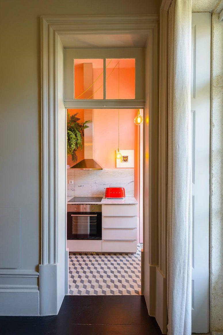 La cuisine présente des armoires blanches, un dosseret en marbre blanc, des murs pêche et de la verdure et des lampes à pied