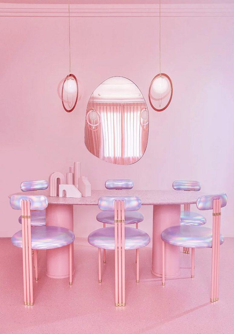 La salle à manger est faite avec une table ovale rose, des chaises irisées et des suspensions plus un miroir de forme étrange