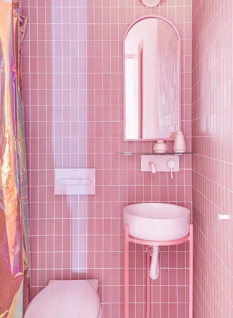 Il y a aussi une autre salle de bain revêtue de carreaux roses, un lavabo rond et un miroir cintré plus un espace douche