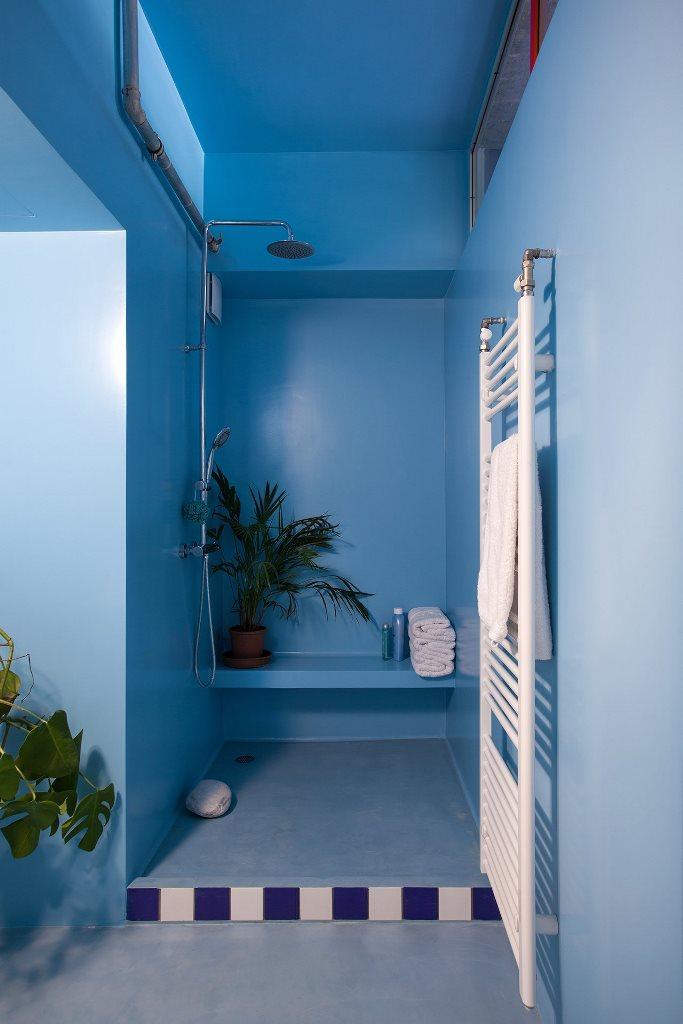 La salle de bain est faite en bleu clair et puissant, avec un coin douche zoy et quelques carreaux lumineux