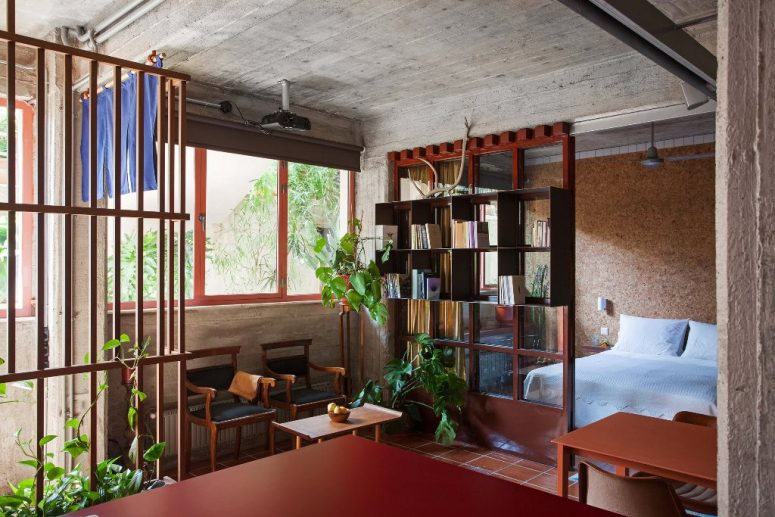 La chambre dispose d'un mur en MDF, il y a des meubles élégants dans les tons bruns et rougeâtres