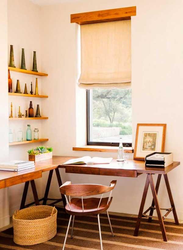 un coin de bureau à la maison rustique confortable avec un grand bureau d'angle à chevalet, des étagères ouvertes, un panier et une chaise en bois ainsi que des stores