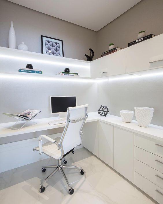 un bureau à domicile minimaliste avec un bureau d'angle et des armoires de rangement sous la surface, des étagères éclairées et des armoires au-dessus
