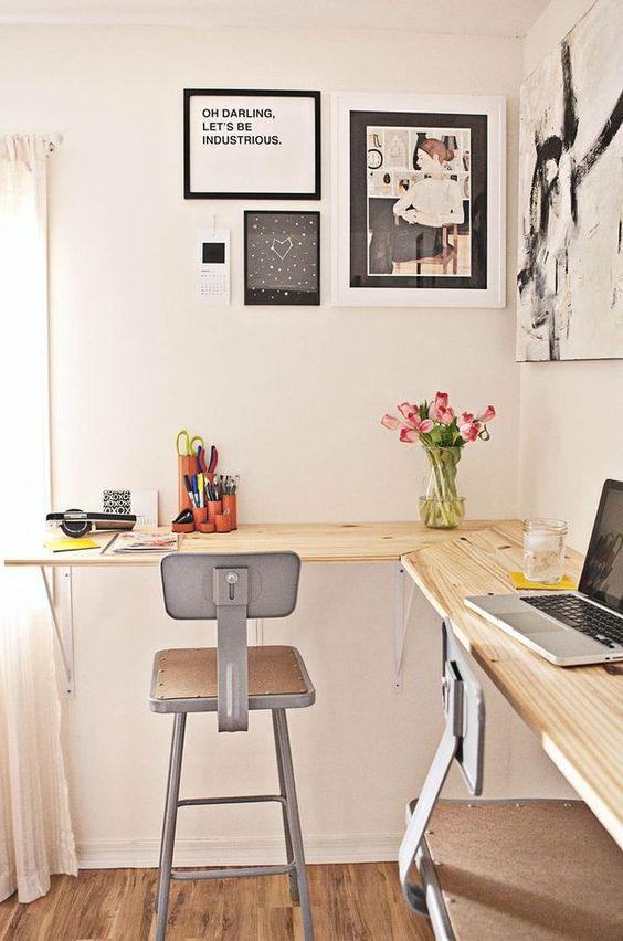 un bureau à domicile industriel moderne avec un bureau flottant en bois, des tabourets en métal, un mur de galerie noir et blanc et des fleurs