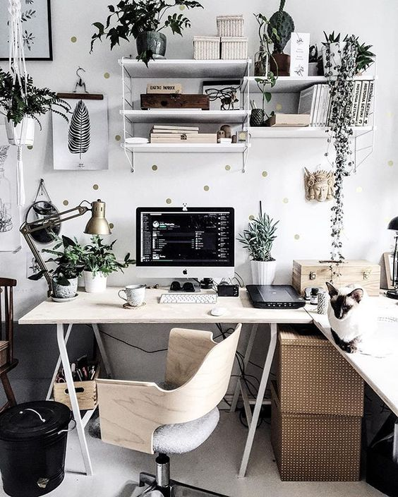 un bureau à la maison scandinave élégant avec un bureau d'angle à chevalet, des boîtes, de la verdure, un mur à pois et une chaise en contreplaqué