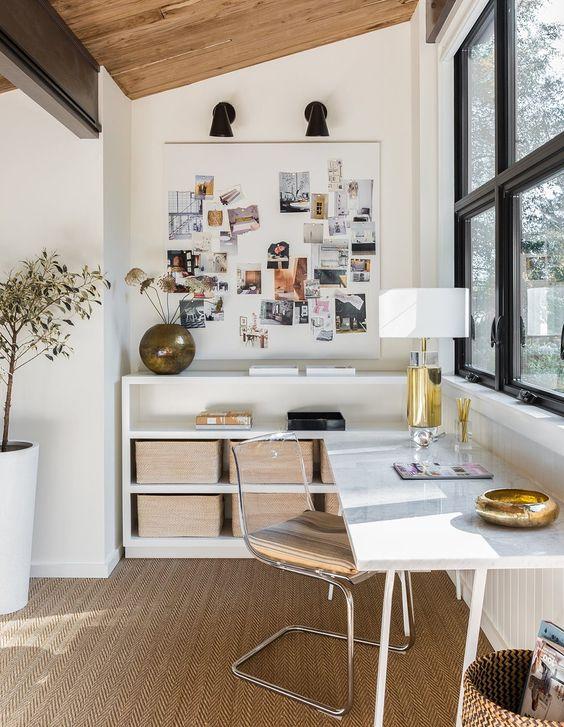 un bureau à domicile élégant et raffiné avec un bureau d'angle et des rangements ouverts, un tapis en jute et une chaise en acrylique est très chic