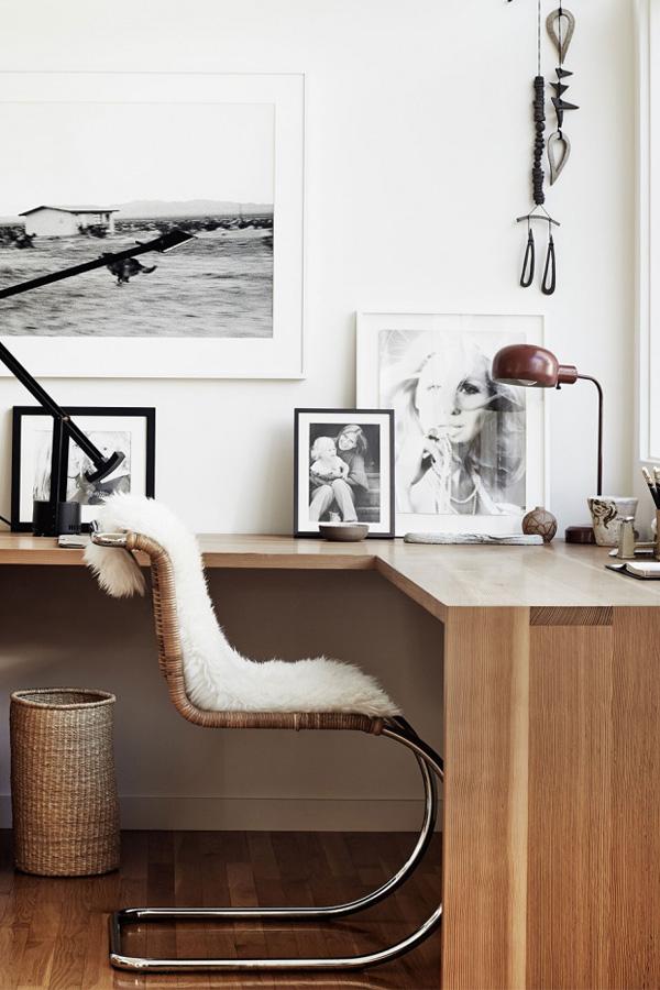 un coin bureau scandinave avec un bureau d'angle flottant, un mur de galerie, une chaise en rotin et un panier ainsi que de la fausse fourrure