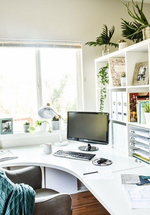 un bureau à la maison contemporain élégant en blanc, avec un bureau d'angle incurvé et un meuble de rangement ouvert, une chaise confortable et un peu de verdure