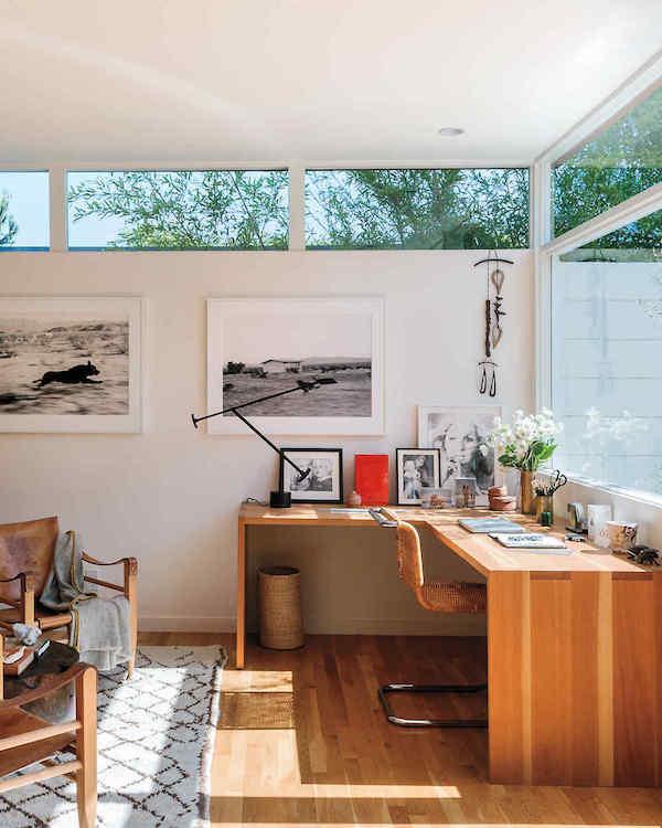 un bureau à la maison moderne et élégant avec un grand bureau d'angle avec de nombreuses œuvres d'art et une belle vue sur l'extérieur