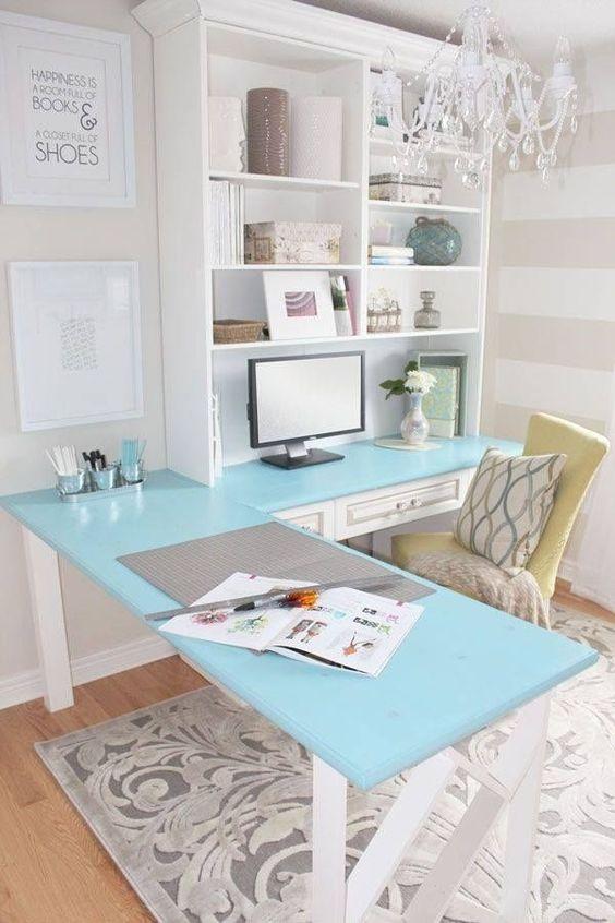 un bureau à domicile de ferme vintage avec un bureau d'angle bleu et une unité de rangement d'un côté, une chaise jaune et un lustre en cristal glam