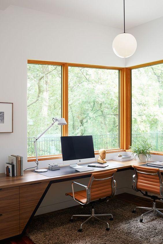 un élégant bureau à domicile moderne du milieu du siècle avec un bureau d'angle en bois chic, des chaises en cuir et de grandes fenêtres pour profiter de la vue