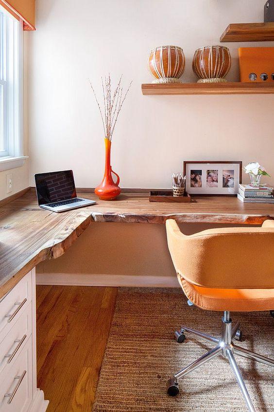 un bureau à domicile aux couleurs chaudes avec un bureau d'angle Live Edge, une chaise jaune, des étagères ouvertes et un vase orange
