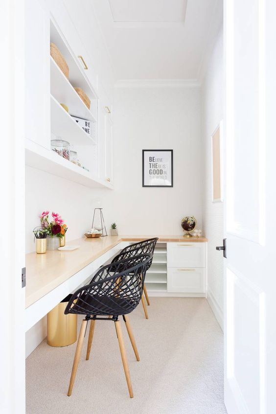 un petit bureau à domicile blanc avec un bureau d'angle partagé et des armoires sous la surface, une grande armoire ouverte et des chaises tissées noires