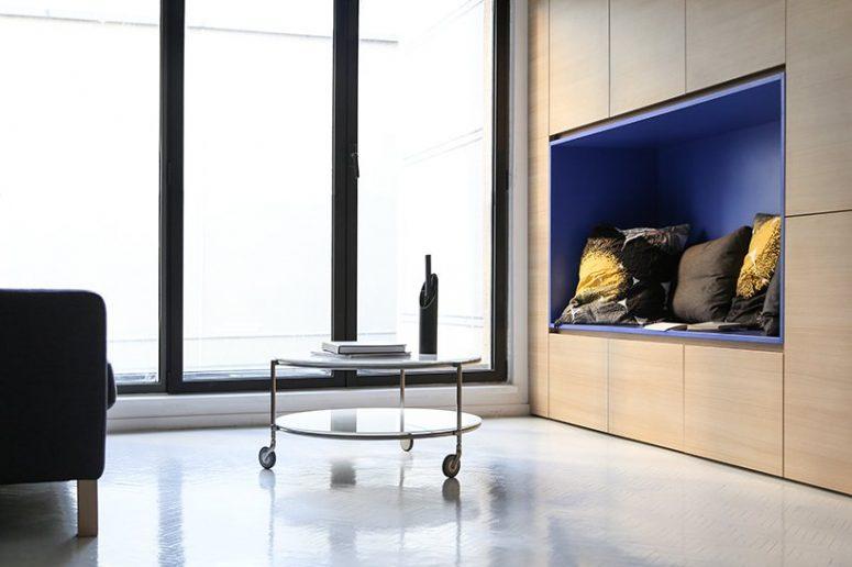 Une alcôve bleue offre une enceinte confortable et abritée pour lire près de la fenêtre