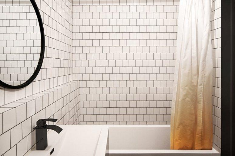 La salle de bain est contemporaine, avec des carreaux blancs et du coulis noir et des accents plus noirs pour le drame