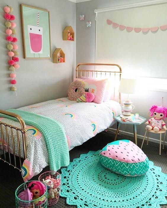 une chambre d'enfant lumineuse et pastel avec des guirlandes colorées, de la literie, des jouets, des tapis et des oreillers gourmands sympas