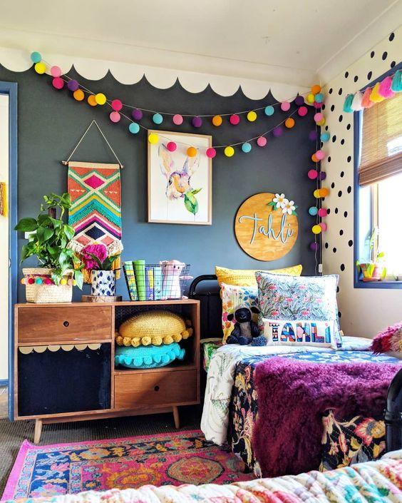 une chambre d'enfant lumineuse avec un mur noir, des guirlandes de pompons colorées, des oreillers, de la literie et un tapis est très audacieuse