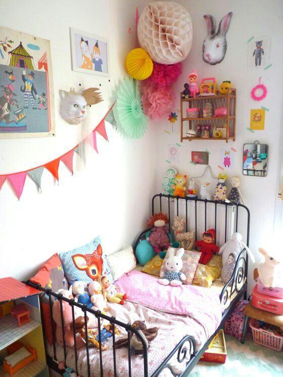une chambre d'enfant audacieuse avec des œuvres d'art colorées, des accessoires et des jouets, une literie colorée, des pompons et des guirlandes