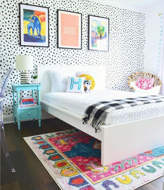 une chambre d'enfant colorée avec un mur Dolmatin, une literie colorée et un tapis, des œuvres d'art audacieuses, une table de chevet bleue et une chaise en rotin